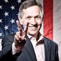 Older man with gray sideburns smiling and holding his fingers in a peace sign with a flag in the background