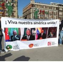 People holding a big banner outside that says Viva nuestra america unida! and a lot of faces of people