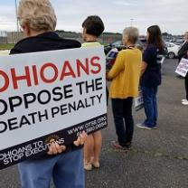 The backs of four people at a vigil outside one holding a sign that says Ohioans Oppose the Death Penalty