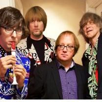 Four white guys one playing a kazoo and looking like rock stars except one guy in the middle with a sport coat on