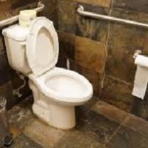 White toilet with lid up and toilet paper roll on hanger on wall under a silver bar against a brown tile wall and floor