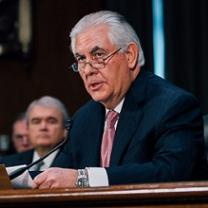 Older man with gray hair, a dark suit and pink tie sitting at a mic with glasses halfway down his nose