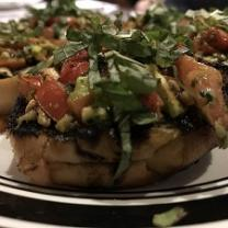 A piece of food on a plate with other similar items, looks like a baked potato with lots of greens, tomatoes, other brownish things on top.