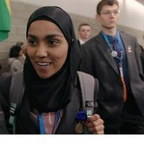 Young dark skinned woman in a burqa smiling and a young white man in a suit looking serious behind her
