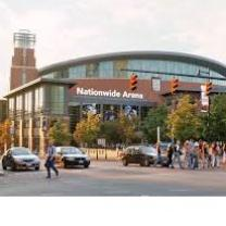 Big brick building with rounded top and lots of people out front and words on it Nationwide Arena