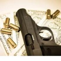 Dark gray handgun lying sideways on a table with gold bullets strewn around it