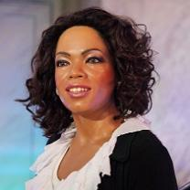 Photo of black woman with shoulder length black curly hair wearing a black top with white collar smiling at the camera