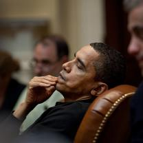 Obama leaning back in leather chair with hand on mouth looking pensive