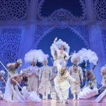 Fancy costumed people against blue theater backdrop like a castle inside, feathered headdresses, dancing