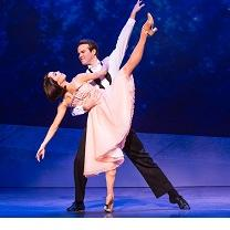 White man with dark hair in white shirt and black pants dancing with a white woman with short dark hair in a pick dress, he is leaning over as he holds her as she is kicking her leg high up in the air
