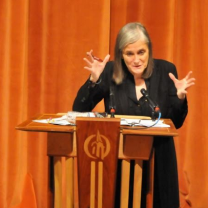 Amy gesturing with both hands at a podium