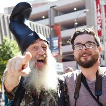 Guy with white beard and funny hat standing next to young man with glasses