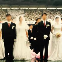 Two couples, grooms in black suits and women in long white wedding dresses