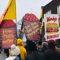 People marching with very large high signs with depictions of barrels of tomatoes with the words How much longer? and Join the Fair Food program and a Wendy's hamburger that says violence on it