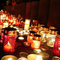 Lots of gold and red candles glowing in the dark