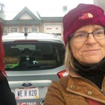 Carolyn on the right, blonde woman with maroon winter hat and glasses standing next to car with Native American woman on right