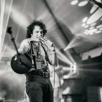 Black and white photo of young dark haired man singing into a mic on a stage