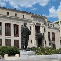 Big governmental building with statue of Christopher Columbus in front, some bushes against a blue sky with white clouds