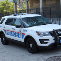 White SUV police vehicle with red and blue on the side saying POLICE