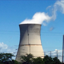 Big fat nuclear plant smokestack with white smoke billowing out against a blue sky