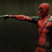 Deadpool character pointing a gun at a teddy bear