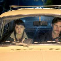 Man and young woman in front seat of car