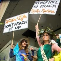 Two women dressed in gowns with protest signs saying Don't Frack it up and It's not nice to frack mother nature