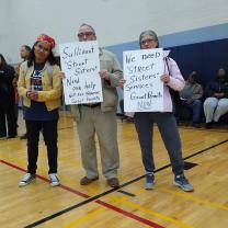 Esther and Gary Witte and Winie Wirth holding signs