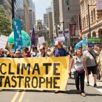 People marching with large banner about climate catastrophe