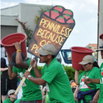 Dark-skinned men and women in green shirts at a demonstration marching to the left one holding a sign saying Penniless because of and two others holding big rust colored buckets
