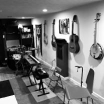 Black and white photo of room with lots of guitars and a banjo hanging on the wall and other musical instruments