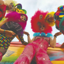 Camera angle looking from ground up at four decked out women with bright orange, pink and rainbow colored fluffy feathery bedazzled outfits