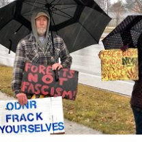 Two people standing outside in the rain holding umbrellas and signs, one says ODNR Frack Yourselves