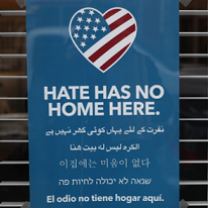 Blue sign with a heart that has a flag and words Hate has no home here