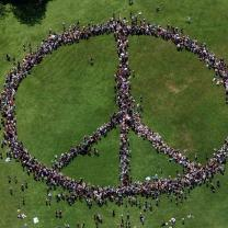 People standing as a peace sign from a distance