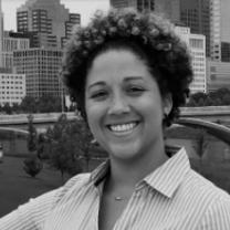 Smiling black woman with short cropped curly hair and a striped button down shirt standing with downtown buildings and a bridge across the river behind her