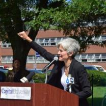 Jill Stein raising her fist at the podium