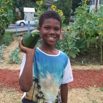 Young black boy smiling and holding a very large zucchini on his shoulder, standing in a garden
