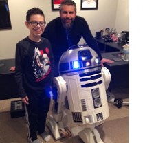 Man and young boy posing next to a robot that has a round top and white round body