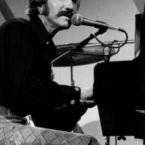 Black and white photo of guy with big mustache sitting at piano singing