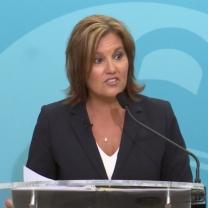 White woman in a black suit with white shirt underneath and necklace with shoulder length brown hair standing at a mic with a blue background, her mouth in a form like she's talking