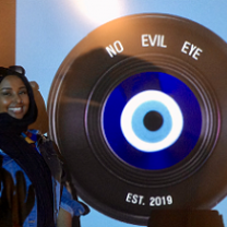 Black woman standing next to a large film reel that says No Evil Eye on it