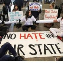 People sitting in a circle on the ground with signs, one in the middle says No hate in our state