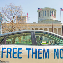 Car with sign saying Free Them Now in front of Ohio Statehouse