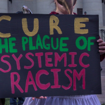 Sign saying Cure the Plague of Systemic Racism