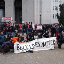 People wearing winter clothes bending down on one knee outside holding a long white banner with black letters reading Black Lives Matter in front of a large white building
