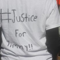 The back of a person wearing a white T-shirt that says Justice for Timmy!!