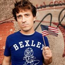 Young brown haired man wearing a blue t-shirt saying Bexley and waving a tiny flag in front of some kind of wall with words on it