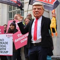 Man wearing Trump mask at demonstration with people holding signs saying No Trade Deal with Trump
