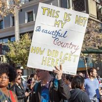 "Guy holding sign saying ""This is not my beautiful country, how did I get here?"